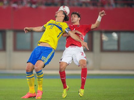 camaraderie: VIENNA, AUSTRIA - SEPTEMBER 9, 2014: Aleksandar Dragovic (#3 Austria) and Zlatan Ibrahimovic (#10 Sweden) fight for the ball in an European Championship qualifying game.