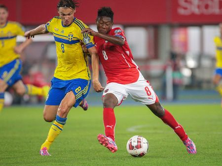 9 ball: VIENNA, AUSTRIA - SEPTEMBER 9, 2014: Albin Ekdal (#8 Sweden) and David Alaba (#8 Austria) fight for the ball in an European Championship qualifying game.