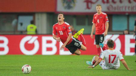 camaraderie: VIENNA, AUSTRIA - OCTOBER 12, 2014: Elsad Zvertovic (#17 Montenegro) fouls Zlatko Junuzovic (#10 Austria) in an European Championship qualifying game. Editorial