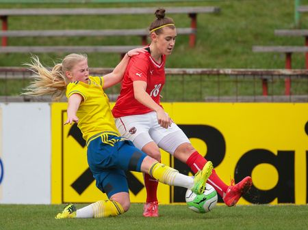 camaraderie: SANKT POELTEN, AUSTRIA - APRIL 13, 2015: Ida Stroemblad (#7 Sweden) and Laura Krumboeck (#18 Austria) fight for the ball during a UEFA womens U17 qualifying game.