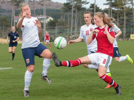 action girl: LINDABRUNN, AUSTRIA - APRIL 13, 2015: Julie Hansen (#8 Denmark) and Emma Andersen (#3 Norway) fight for the ball during a UEFA womens U17 qualifying game.