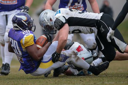 VIENNA, AUSTRIA - MARCH 22, 2015: LB Philipp Margreiter (#36 Raiders tackles RB Islaam Amadu (#20 Vikings) in a game of the Austrian Football League. Editorial
