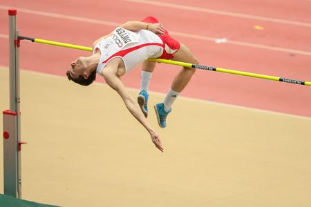 competes: LINZ, AUSTRIA - FEBRUARY 6, 2015: Rory Dwyer (#411 Great Britain) competes in the mens high jump event in an indoor track and field event.