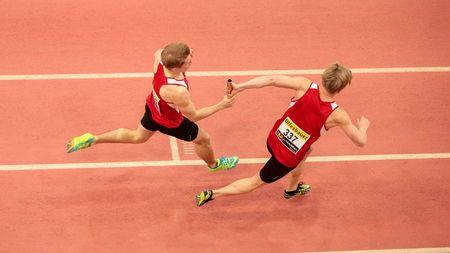 carrera de relevos: LINZ, AUSTRIA - FEBRERO 22 de, 2015: Dustin Jordan Hnili?ka (# 337) y Paul Schuster (# 338 Austria) compiten en prueba de relevos 4x200 de los hombres en un evento de atletismo bajo techo.