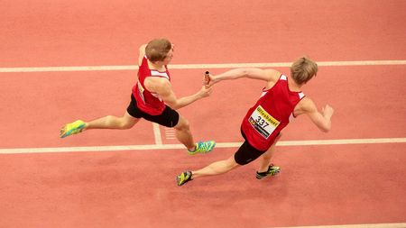 LINZ, AUSTRIA - FEBRUARY 22, 2015: Dustin Jordan Hnilicka (#337) and  Paul Schuster (#338 Austria) compete in the mens 4x200m relay event in an indoor track and field event. Editorial