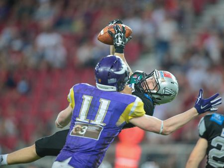 db: KLAGENFURT, AUSTRIA - JULY 11, 2015: DB Vincent Müller (#23 Raiders) tackles WR Manuel Thaller (#11 Vikings)  in a game of the Austrian Football League.