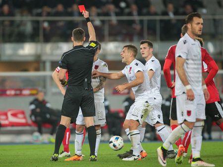 VIENNA, AUSTRIA - MARCH 26, 2016: Referee Ivan Kruzliak (Slovakia) shows the red card to Ergys Kace (Albania)  in a friendly football game. Editorial