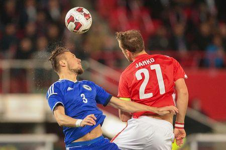 hombre deportista: VIENA, Austria - 31 de marzo, 2015: Ermin Bicakcic (# 3 Bosnia-Herzegovina) y Marc Janko (# 21 Austria) lucha por el balón durante un partido de clasificación para el Campeonato Europeo.
