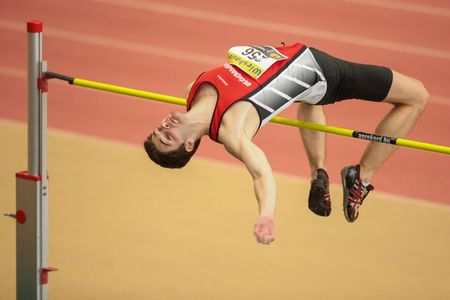 competes: LINZ, AUSTRIA - FEBRUARY 22, 2015: Alexander Dengg (#256 Austria) competes in the mens high jump event in an indoor track and field event.