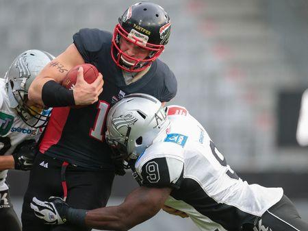 lb: INNSBRUCK, AUSTRIA - APRIL 11, 2015: LB Wendel Brown (#9 Raiders) tackles QB Manuel Engelmann (#15 Panther) in a game of the Big Six Football League.