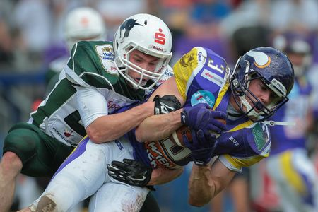 VIENNA, AUSTRIA - MAY 17, 2015: CB Christian K�ppe (#21 Unicorns) tackles WR Dominik Bundschuh (#3 Vikings) in a game of the Big Six Football League. in a game of the Big Six Football League.