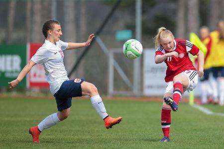 camaraderie: LINDABRUNN, AUSTRIA - APRIL 13, 2015: Siw Doevle (#10 Norway) and Anne Katrine Hansen (#17 Denmark) the ball during a UEFA womens U17 qualifying game.