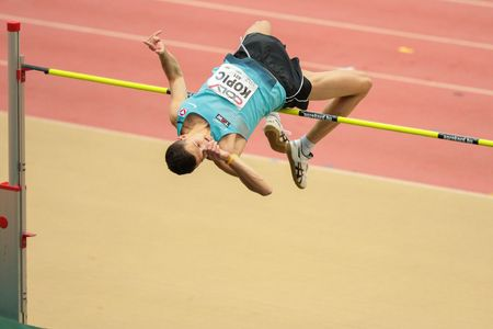 competes: LINZ, AUSTRIA - FEBRUARY 6, 2015: Josip Kopic (#401 Austria) competes in the mens high jump event in an indoor track and field event. Editorial