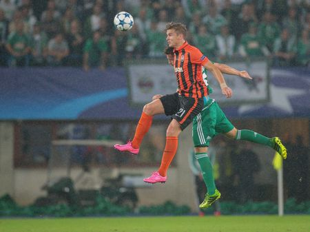 camaraderie: VIENNA, AUSTRIA - AUGUST 19, 2015: Olexandr Gladkiy (FC Shakhtar) and Thanos Petso (SK Rapid) fight for the ball in an UEFA Champions League qualification game.