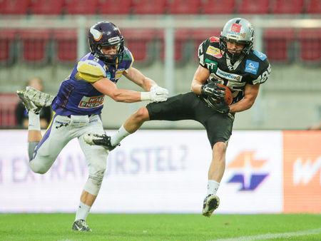 db: KLAGENFURT, AUSTRIA - JULY 11, 2015: DB Christoph Gombkoetoe (#9 Vikings) tackles WR Julian Ebner (#85 Raiders) in a game of the Austrian Football League.