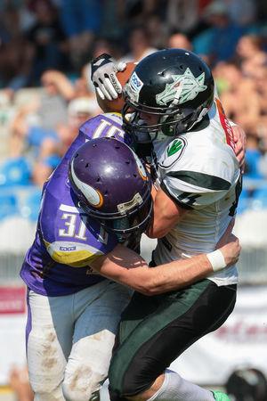 db: VIENNA, AUSTRIA - JULY 5, 2015: DB Gregor Mernyi (#31 Vikings) tackles WR Tobias Morgenbesser (#84 Dragons) in a game of the Austrian Football League.