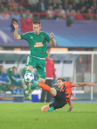 uefa: VIENNA, AUSTRIA - AUGUST 19, 2015: Robert Beric (SK Rapid) and Taras Stepanenko (FC Shakhtar) fight for the ball in an UEFA Champions League qualification game.