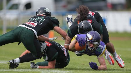 lb: VIENNA, AUSTRIA - MAY 31, 2015: LB Ramon Azim (#25 Dragons) tackles WR Dominik Bundschuh (#3 Vikings) in a game of the Austrian Football League.
