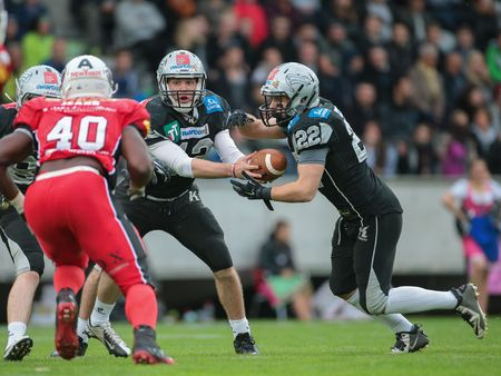 INNSBRUCK, AUSTRIA - MAY 2, 2015: QB Sean Shelton (#12 Raiders) hands the ball to RB Fabien-André Gärtner (#22 Raiders) in a game of the Big SIx Football League. Editorial