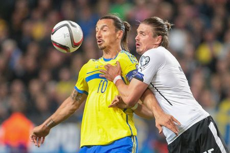 camaraderie: STOCKHOLM, SWEDEN - SEPTEMBER 8, 2015: Zlatan Ibrahimovic (Sweden) and Sebastian Proedl (Austria) fight for the ball in an European Championship qualification game.