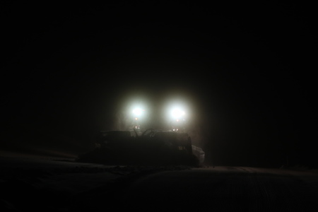snowcat at night searchlight