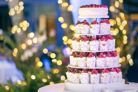 esküvő: Édes esküvői torta készült friss bogyós cupcake háttér bokeh.