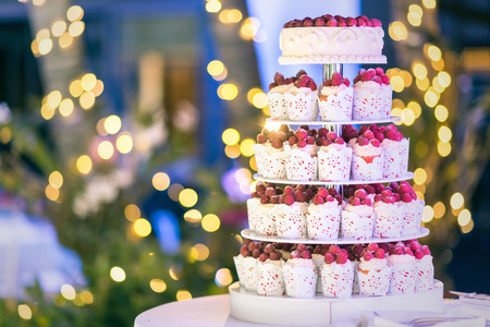 cake stand: Sweet wedding cake made from fresh berry cupcake with bokeh background.