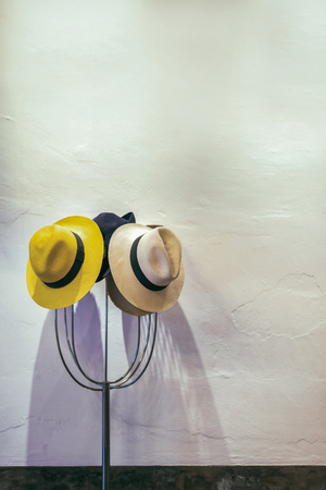 to old clothes: Sombreros en percha, la pared de fondo blanco, enfoque selectivo.