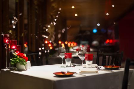 ロマンス: ロマンチックなディナー レストランでキャンドル ライトのセットアップ、赤い装飾。選択と集中。