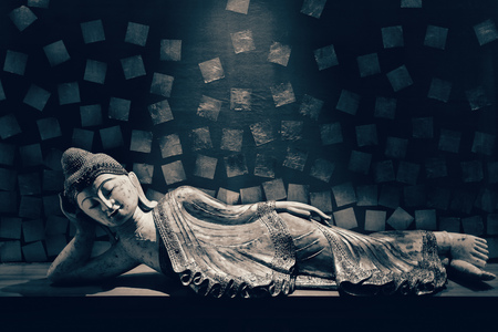 religious: Antique carved wooden Buddha, reclining Buddha posture. selective focus. Stock Photo