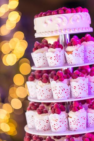 背景のボケ味と新鮮なベリーのカップケーキから作られた甘いウェディング ケーキ。 写真素材