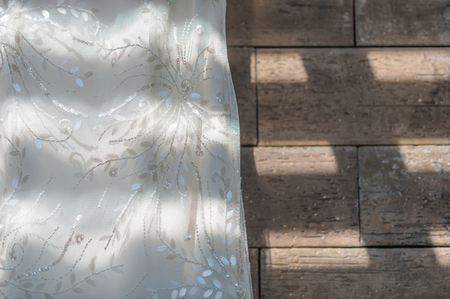 brown granite: Wedding dress close up hanging on brown granite background, painted with light and shadow.