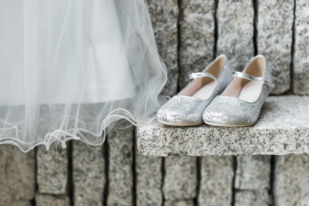 dress up: A childs wedding dress hanging up  with silver shoes beside on granite background.
