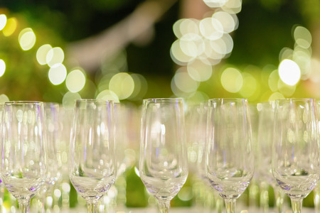 fizzy tablet: Row of wine glasses in green background painted with beautiful bokeh. Stock Photo