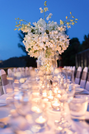wedding table decor: Romantic dinner setup, decoration with candle light. Selective focus. Stock Photo