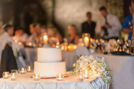 The white wedding cake, decorated with the silver soil, party background. Selective focus.