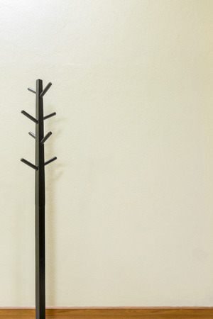 input: Black wooden coat rack on wall background, space for input text.