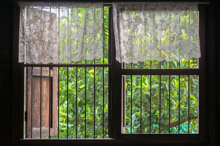 iron curtains: Old style Thai window with top-half lace curtain.