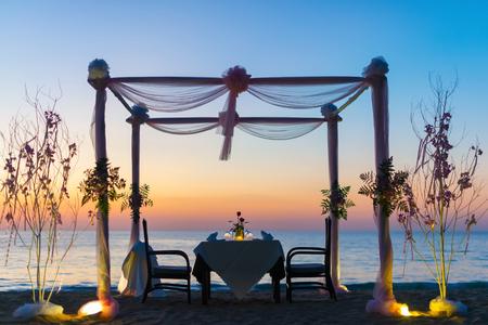 réglage de dîner romantique sur la plage au coucher du soleil.