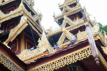 red cross red bird: Pigeons sitting on Thai temple roof with beautiful carvings and decor, painted with red brown and gold. Stock Photo