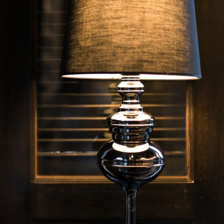 close: Closeup black designed floor lamp on wooden door background.