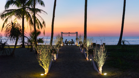 romatic: Loving couple share a romatic dinner, elegant candle light setup, sunset on the beach.