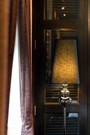 floor lamp: Closeup black designed floor lamp on wooden door background.
