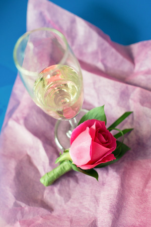 mulberry paper: Rose bouquet for groom on pink mulberry paper and a glass of champagne. Shallow DOF. Stock Photo