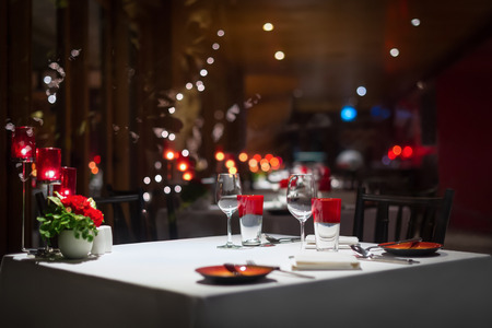candle light table setting: dinner table setting, red decoration with candle light in a restaurant. Selective focus.
