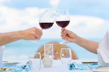 hombre rojo: Pareja beber vino en la cena romántica en twighlight, primer plano. Enfoque selectivo, profundidad de campo.
