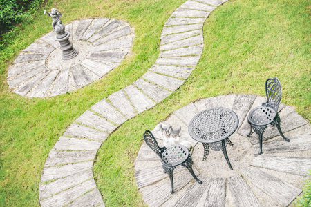 garden furniture: Vintage style garden design, table set for two furniture, stucco, walkway and green grass.