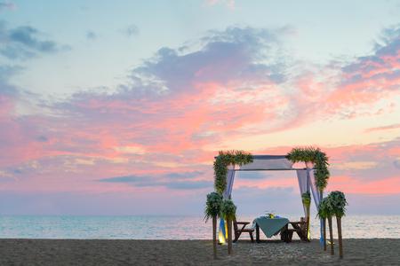 Romantic dinner setting on the beach at sunset. Copy sapce.