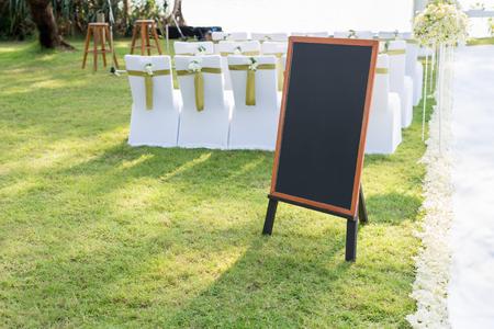 leeres Tafelzeichen mit braunem Holzrahmen vor Hochzeitszeremonie. Hochzeitsdekoration