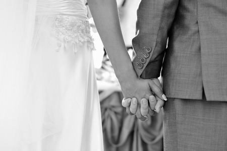 wedlock: Groom holding brides hand in outdoors wedding, holding hands newlyweds. Stock Photo